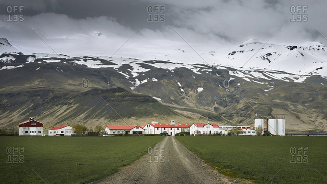 Road leading to a farm below mountain in Iceland