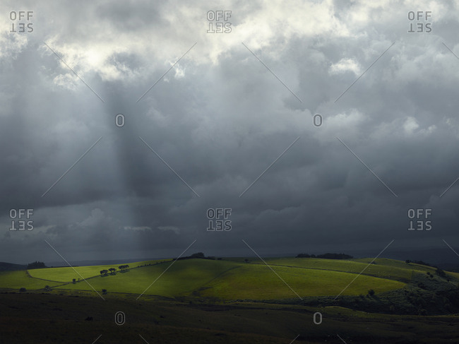 Sunlight streaming through clouds in Welsh countryside