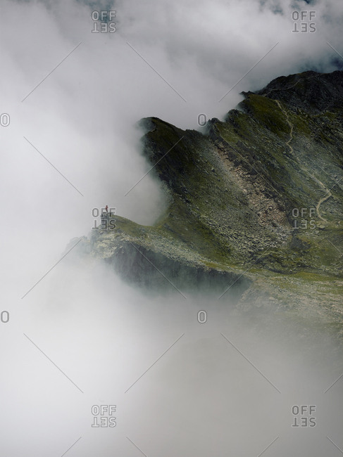 Person on cliff stands before incoming fog