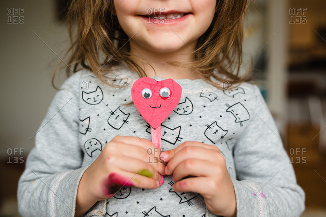 Little girl holding a popsicle stick and paper heart craft