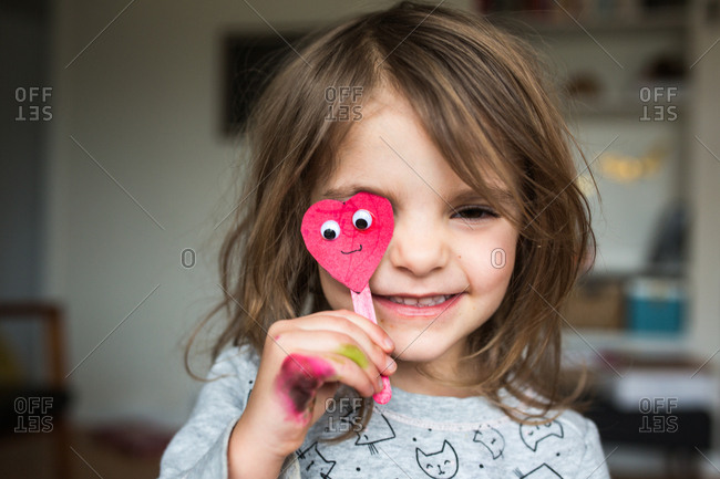 Little girl making a silly face with a paper heart on a popsicle stick