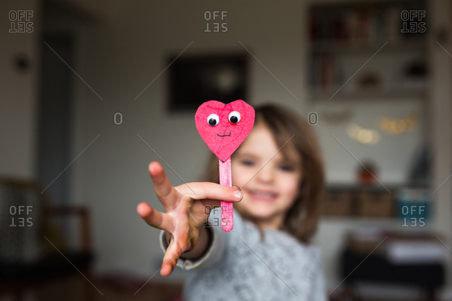 Little girl showing off a craft made from a popsicle stick and paper heart