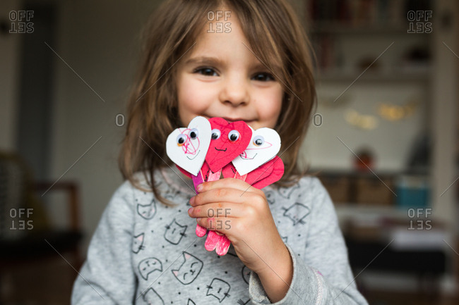 Little girl holding crafts made from paper hearts and popsicle sticks