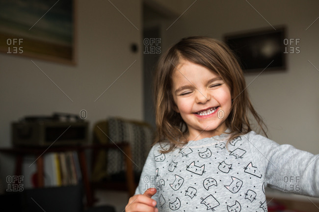 Little girl grinning with her eyes closed
