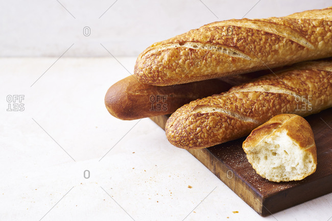 Fresh baked loaves of bread on cutting board on white counter