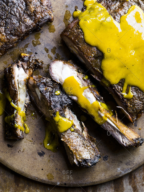 Barbecued beef ribs topped with mustard