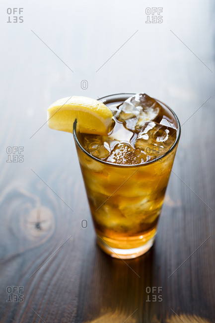 Beverage with lemon wedge on wooden table