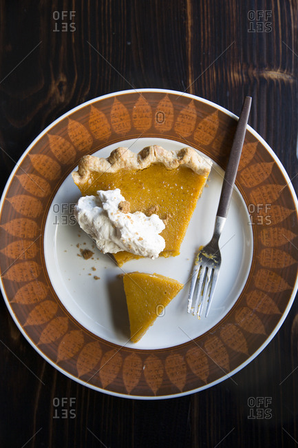 Overhead view of a slice of pumpkin pie with whipped topping