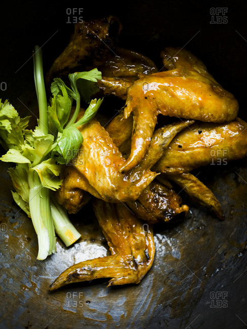 Chicken wings in a bowl with sauce and celery