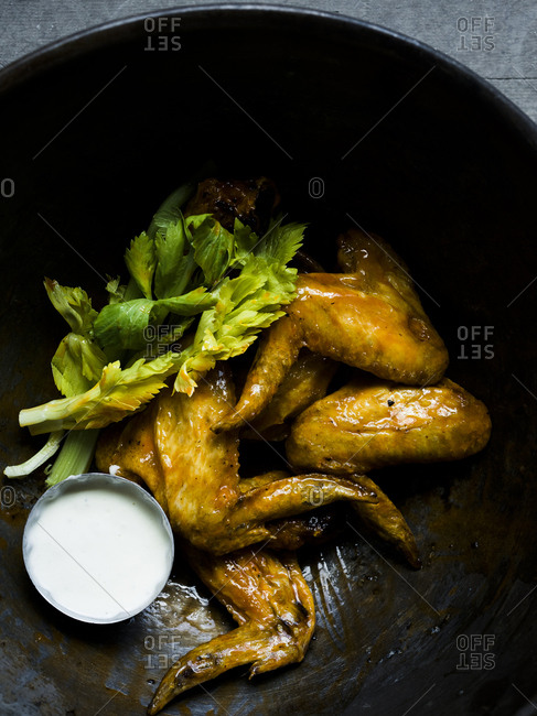 Chicken wings in a bowl with celery and dipping sauce