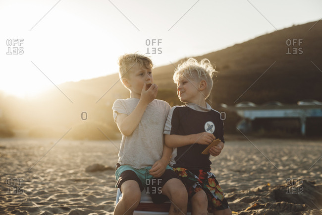 Two boys sitting together on a cooler eating a snack