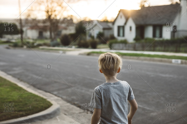 Boy standing in driveway looking out over neighborhood