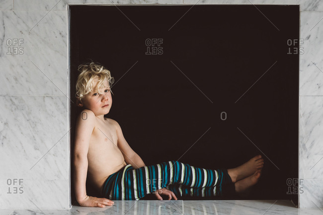Boy leaning against side of alcove opening in marble wall
