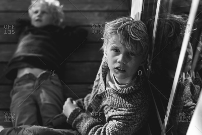 Portrait of a boy wearing a sweater sitting on deck with brother