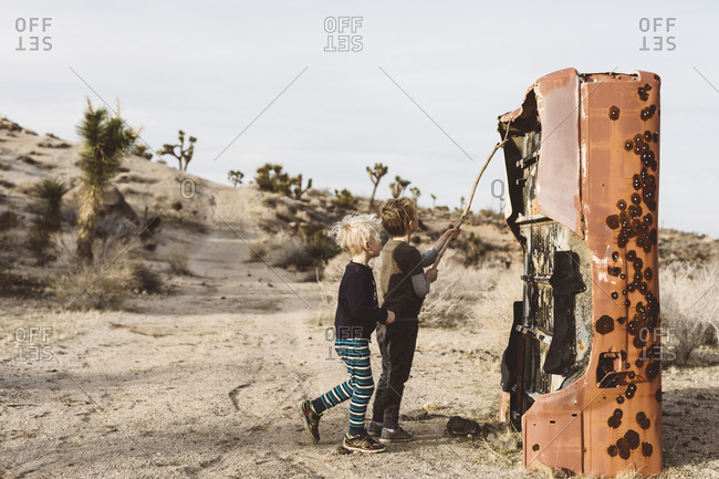 Boy using a stick to poke at remnants of a section of an old rusted truck along a dirt road in the desert