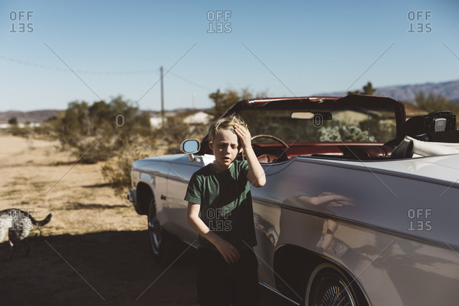 Boy with hand on head standing next to convertible car parked along the side of dirt road in the desert