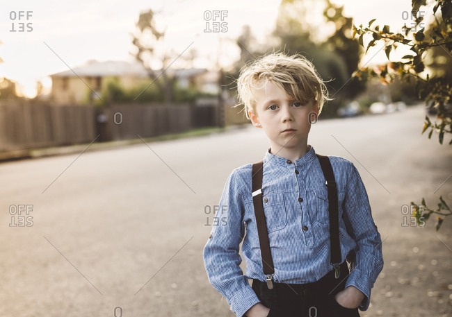 Portrait of a boy wearing a striped shirt and suspenders standing outside in neighborhood