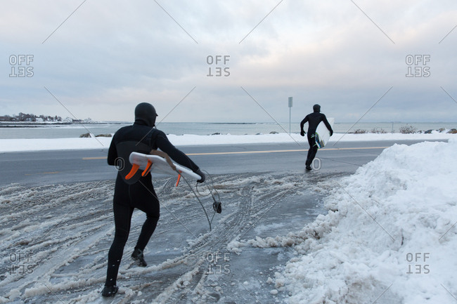 Two men running across a street carrying surfboards in winter