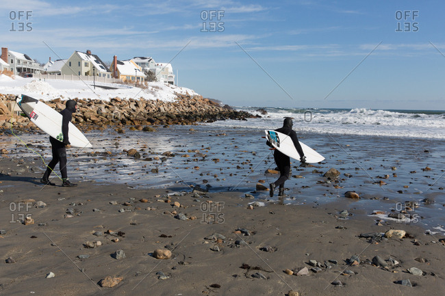 Maine, USA - February 14, 2017: Two men surfing on a rocky beach in winter