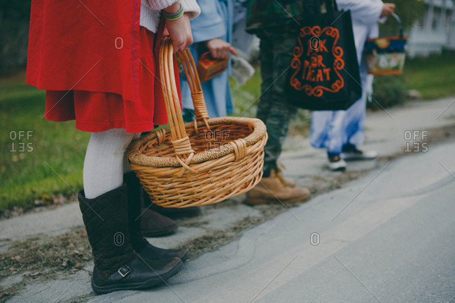 Children trick or treating with baskets and bags