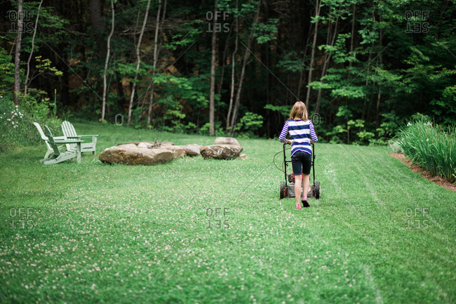 Rear view of a blonde girl mowing grass