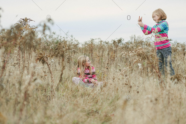 Two girls playing together in an overgrown field