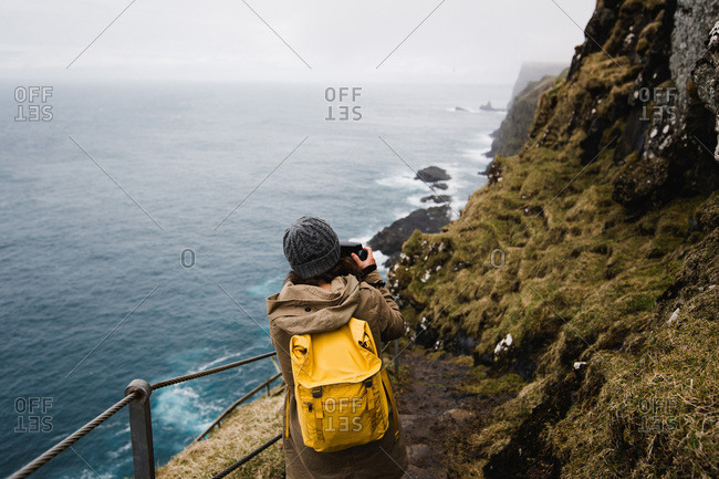 Young woman takes an instant photo of waves crashing into a cliff
