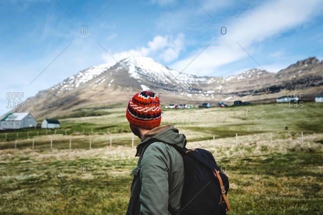 Young man gazing at a snowy peak, Faroe Islands