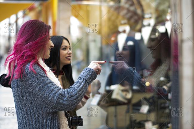 Two young women shopping and looking shop showcase glass. Jaen, Spain.