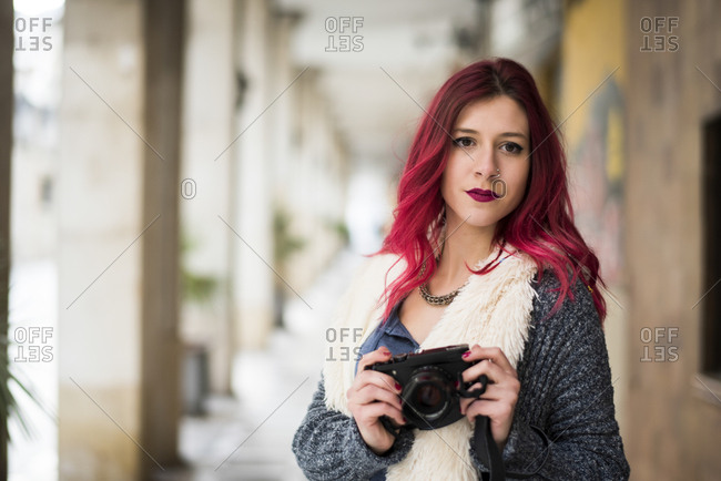 Modern red haired photographer in street reviewing photos. Jaen, Spain