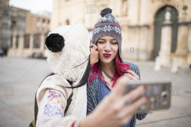 Two young women taking self portraits in European Jaen cathedral square, Spain.