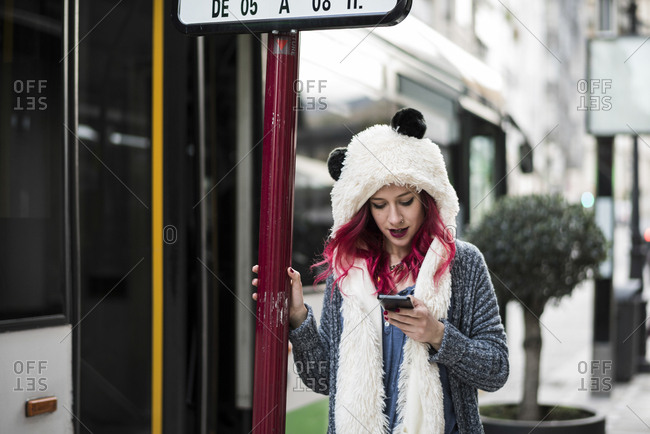 Young woman on her phone while waiting at a bus stop