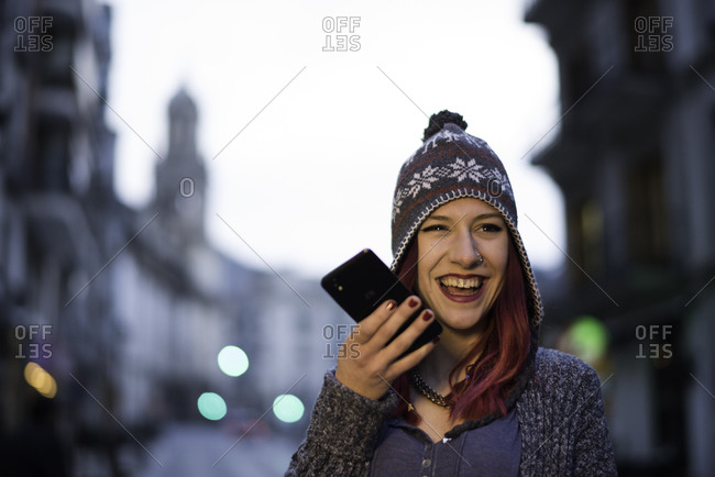 Woman with smartphone walking in the street. Night city scene in Jaen, Spain