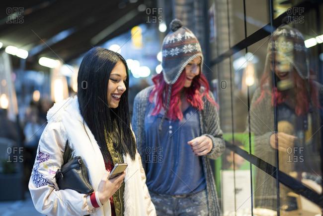 Women in street shopping and talking in city night scene. Jaen, Spain.