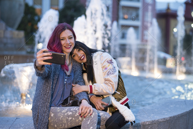 Two young women in fountain taking pictures with smartphone. Jaen, Spain.