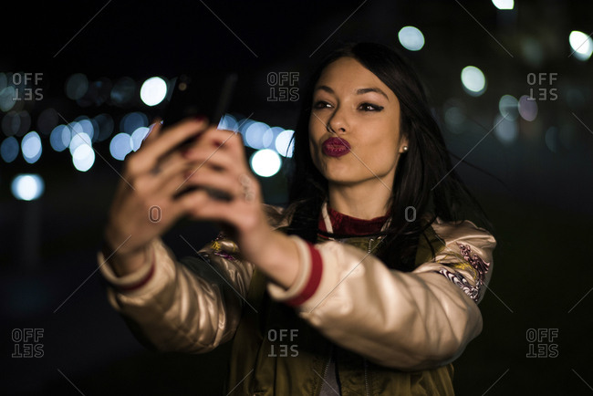 Woman taking self portrait with night bokeh background lights. Jaen, Spain.