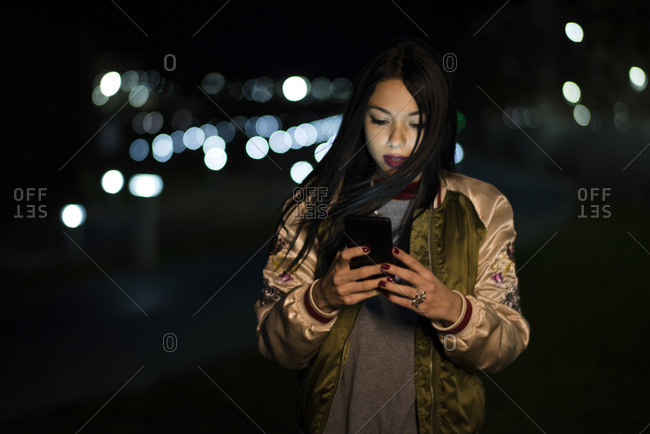 Woman with smartphone sending voice messages with city lights background in Jaen, Spain.