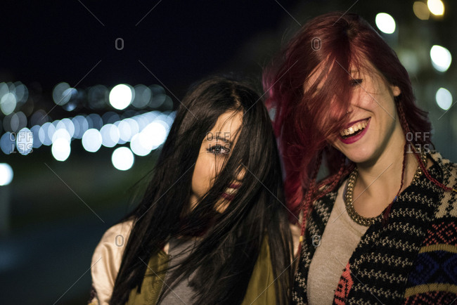 Wind on women hair having fun with night lights in background.