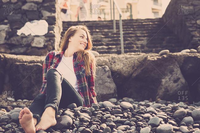 Barefoot woman lounging on rocky coast