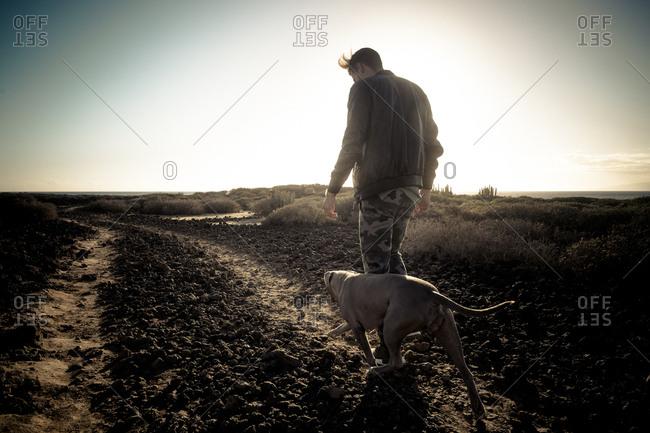 Man and dog walking rocky path