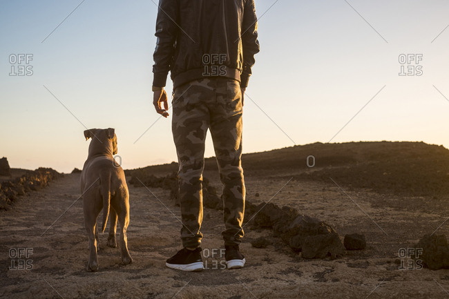 Dog and man stand in barren setting