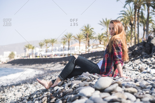 Woman lounging on rocks on beach