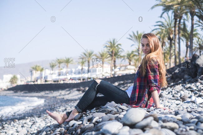 Woman lounging on pebbles on beach