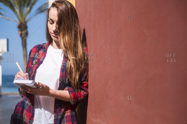 Woman writing by coastal wall