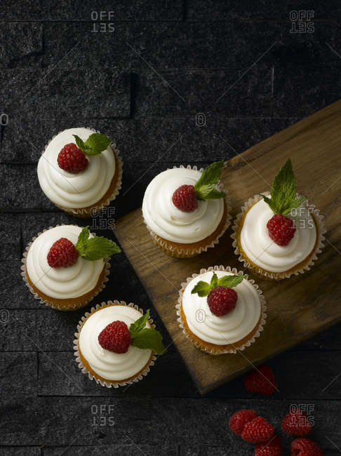 Raspberry and Vanilla cupcakes on a wooden cutting board
