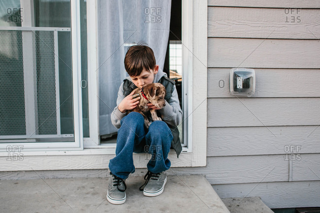 Boy sitting in doorway and kissing his puppy