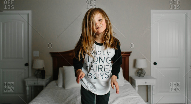 Long-haired boy playing on bed