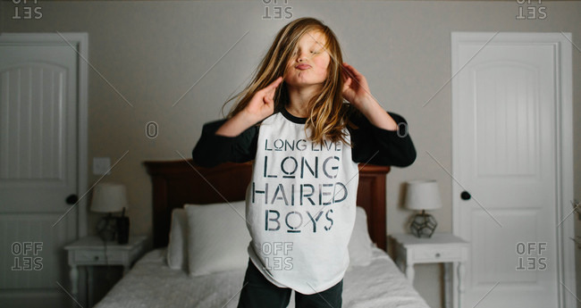 Boy with long hair jumping on bed