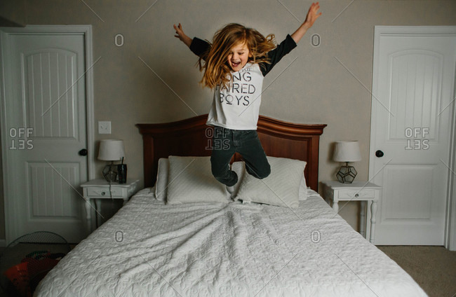 Long-haired boy jumping on bed