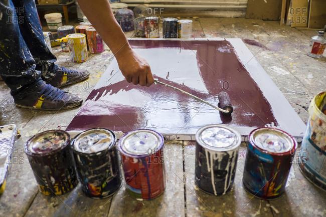 Legs of Mari man painting canvas on floor